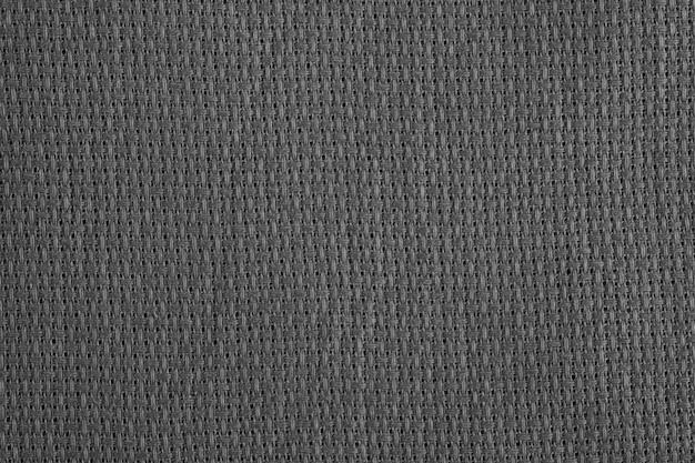 Grijze stoffenclose-up. weven van afzonderlijke draden. gebreid polyester. laagpolige synthetische vezels.