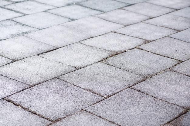 Grijze straatsteen voetgangerspad bestrating close-up van de textuur bovenaanzicht