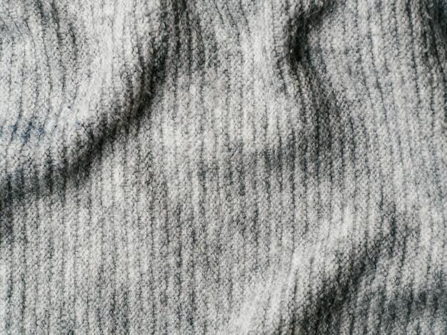 Grijze sweaterstof textuur. kleren trui achtergrond met plooien