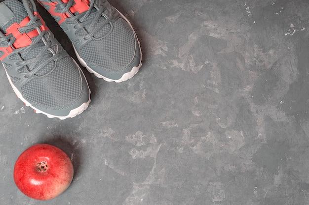 Grijze tennisschoenen, appel op grijze achtergrond. fitness achtergrond