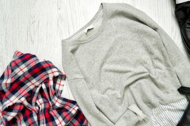 Grijze trui en geruite sjaal. modieus concept