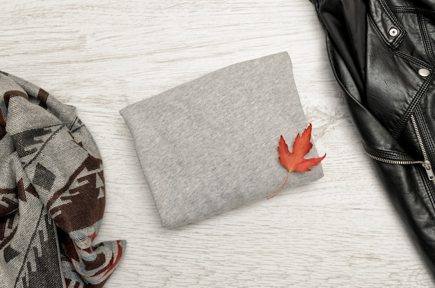 Grijze trui met ruimte voor tekst, een zwart jasje, sjaal en herfstbladeren
