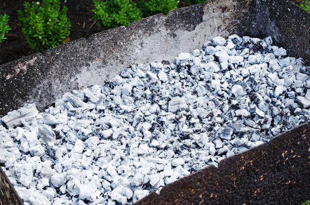 Grijze verbrande kolen in een barbecue. vreugdevuur voor een picknick. zomer, zonnige dag buitenshuis.