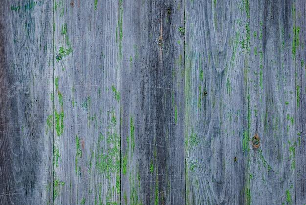 Grijze vervaagde houten muur met resten van afbladderende groene verf en rotplekken