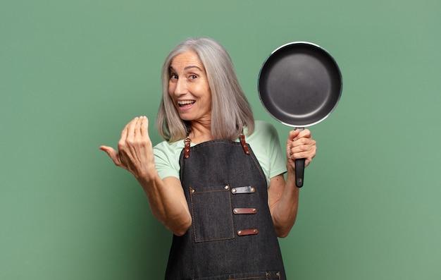 Grijze vrij haar chef-kokvrouw van middelbare leeftijd met een pan