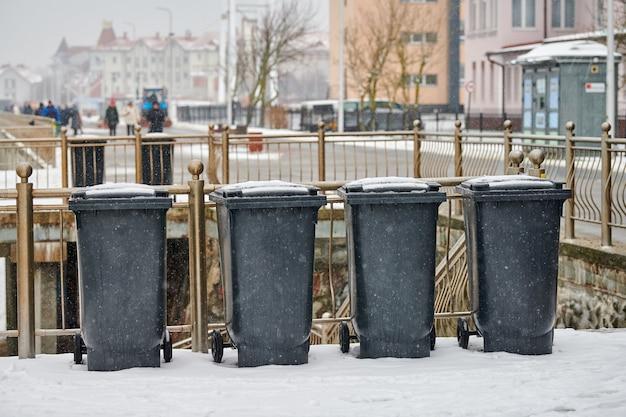 Grijze vuilnisbakken op straat in de winter. openbare afvalcontainers aan de kant van de weg