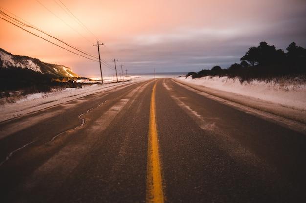 Grijze weg in de buurt van veld bedekt met sneeuw onder witte en oranje hemel