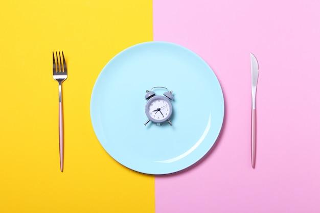 Grijze wekker, vork en mes in lege blauwe plaat op geel en roze. concept van intermitterend vasten, lunch, dieet en gewichtsverlies. bovenaanzicht, plat lag, minimalisme.