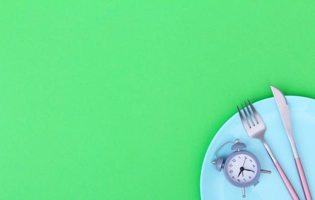 Grijze wekker, vork en mes in lege blauwe plaat op groen. concept van intermitterend vasten, lunch, dieet en gewichtsverlies. bovenaanzicht, plat leggen, minimalisme.