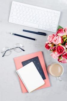 Grijze werkplek bureau tafel met notebooks, lege blanco, leveringen, glazen en kopje koffie.