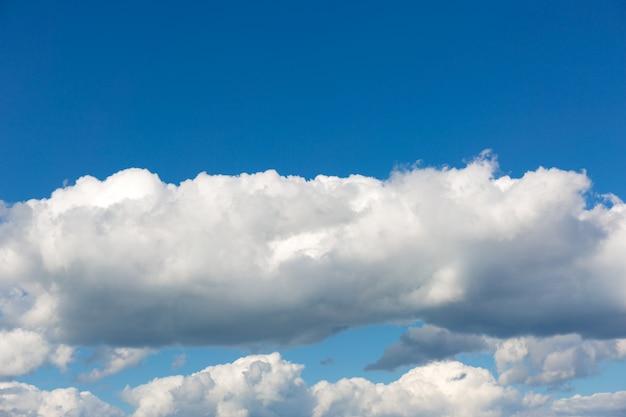 Grijze wolken op blauwe hemelachtergrond.