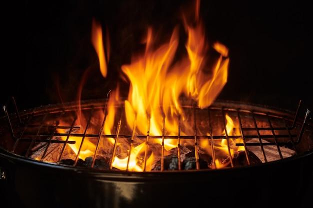 Grill achtergrond. barbecue fire grill close-up, geïsoleerd op zwarte achtergrond