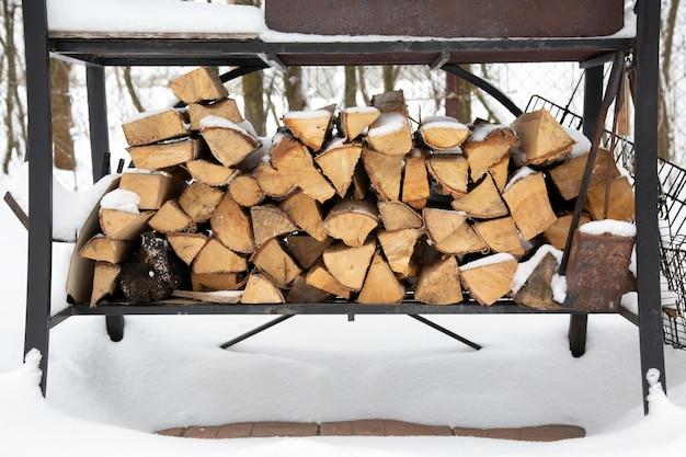 Grill in sneeuwbank. gehakt brandhout van dennen en berken voor bbq onder de sneeuw op straat. wachtend op de zomer.