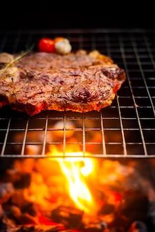 Grillen van t bone steak op vlammende grill