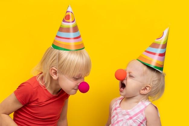 Grillige kinderen gekleed in feestelijke hoeden en rode neuzen