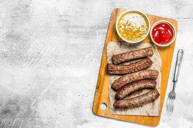 Grillworstjes met verschillende sauzen. op een rustieke tafel.