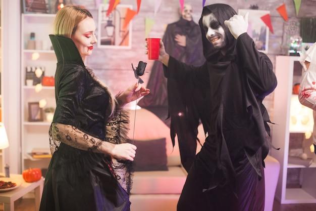 Grim reaper en mooie vampiervrouw die plezier hebben op halloween-feest.