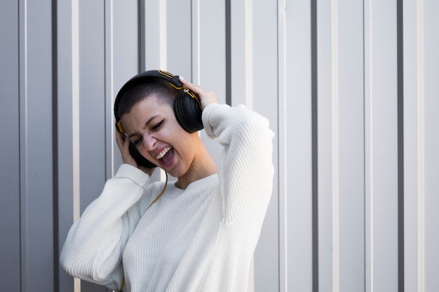 Grimassen jonge vrouw met kort haar luisteren naar muziek in de koptelefoon