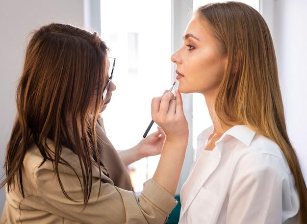 Grimeur die lippenstift op lippen met borstel toepast
