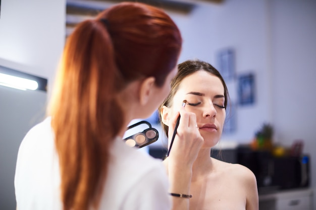 Grimeur die make-up mooi meisje in de salon, schoonheidsconcept en stijl doen.