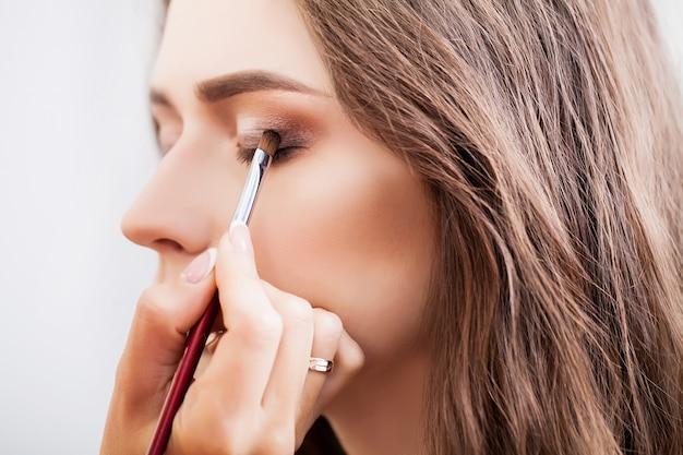 Grimeur die make-upmeisje in de salon doen, schoonheidsconcept