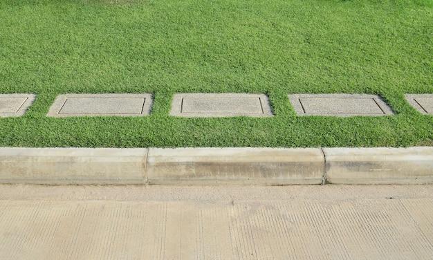 Grinttextuur en strookgras met betonweg als achtergrond