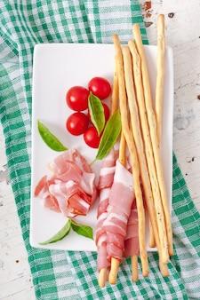 Grissini broodstengels met ham, tomaat en basilicum