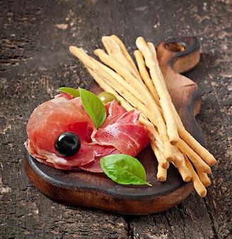 Grissini-broodstokken met ham, olijven, basilicum op oud hout