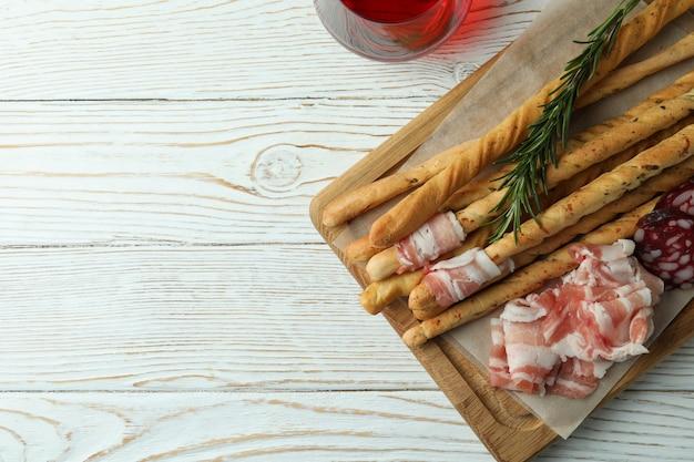 Grissini sticks met spek en wijn op witte houten oppervlak