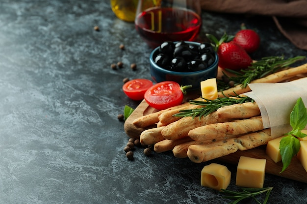 Grissini sticks, snacks en wijn op zwarte smokey achtergrond