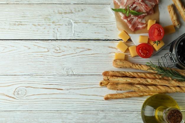 Grissini-stokken en snacks op witte houten oppervlakte