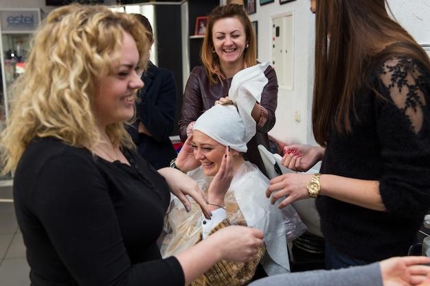 Grodno, wit-rusland - 20 oktober 2016: deelnemers aan het seminar verven het haar van een model op de reclameworkshop van het merk keune in de schoonheidssalon kolibri.