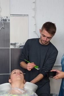 Grodno, wit-rusland - 20 oktober 2016: keune-merktechnoloog artem raychuk verft het haar van een model op een reclameworkshop met deelname aan de schoonheidssalon kolibri.