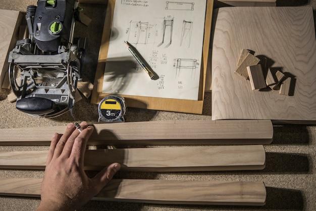Groefmolen, potlood en meetlint, houten spaties en meubelmakerhand met een sigaret