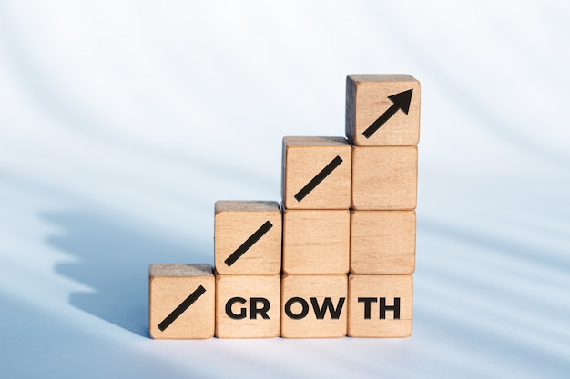 Groei of bedrijfsconcept. pijlpictogram en woord op houten dobbelstenen