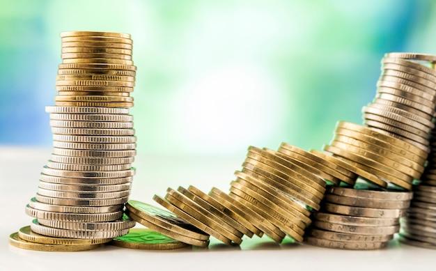 Groeiende muntenstapels met groene en blauwe fonkelende bokeh achtergrond. financiële groei, geld besparen, zakelijke financiën rijkdom en succes concept.