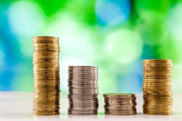 Groeiende muntenstapels met groene en blauwe fonkelende bokeh achtergrond