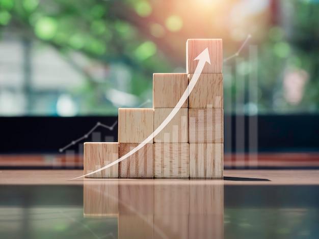 Groeigrafiek en grafiek. gloeiende pijl omhoog op de bovenkant van houten blokken grafiekstappen op houten bureau met kopieerruimte, eco-stijl. het bedrijfsgroeiproces, financiën en economisch verbeteringsconcept.