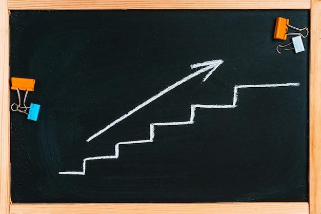 Groeigrafiek met een pijl op een schoolbord, het concept van zakelijke oplossingen en vergaderingen