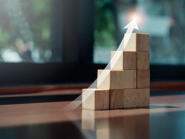 Groeikaart. gloeiende pijl omhoog op de bovenkant van houten blokken grafiekstappen op houten bureau met kopieerruimte, eco-stijl. het bedrijfsgroeiproces, financiën en economisch verbeteringsconcept.