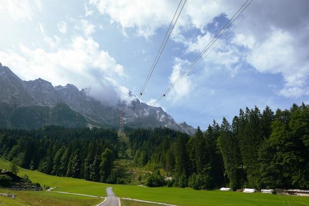 Groen alpenlandschap in het zomerseizoen. groene weiden. het pad dat naar de berg leidt, panoramisch uitzicht - hoogte bereikt door brand-kabelbanen