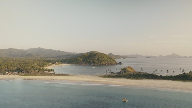 Groen bergeneiland bij de antenne van de oceaanbaai. tropic niemand natuur zeegezicht. rustig zeewater bij zand