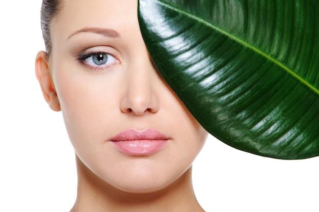 Groen blad dat een mooi vrouwelijk gezicht in de schaduw stelt