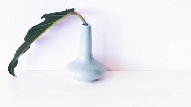 Groen blad in een eenvoudige blauwe vaas
