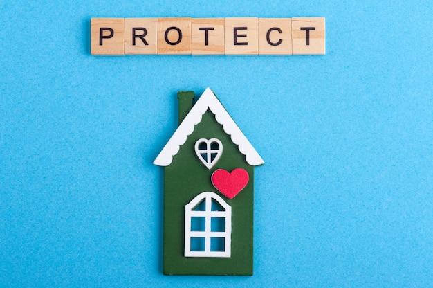 Groen blokhuis en beschermen teken op blauw