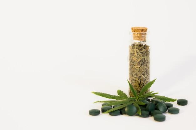 Groen cannabisblad, pillen en droge bladeren
