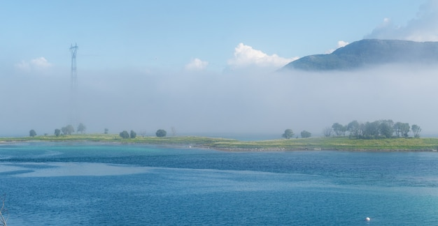 Groen eilandje in een blauwe baai in een mist op een achtergrond van bergen, lofoten, noorwegen