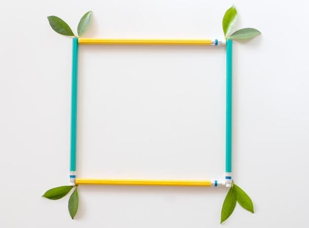 Groen en geel potlodenframe met groene bladeren op witte achtergrond. bovenaanzicht