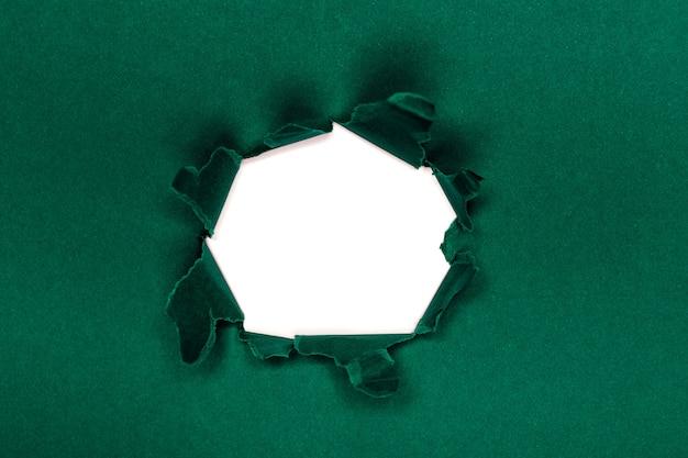 Groen gat in het papier met gescheurde zijkanten