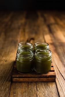 Groen gekleurde alcoholische shooters, of shot drankjes op houten tafel, kopie ruimte